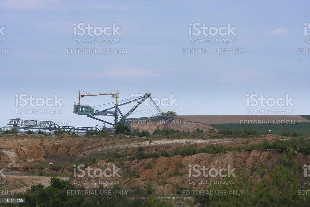 Lignite mining blade destroys farm field in open pit mine stock photo