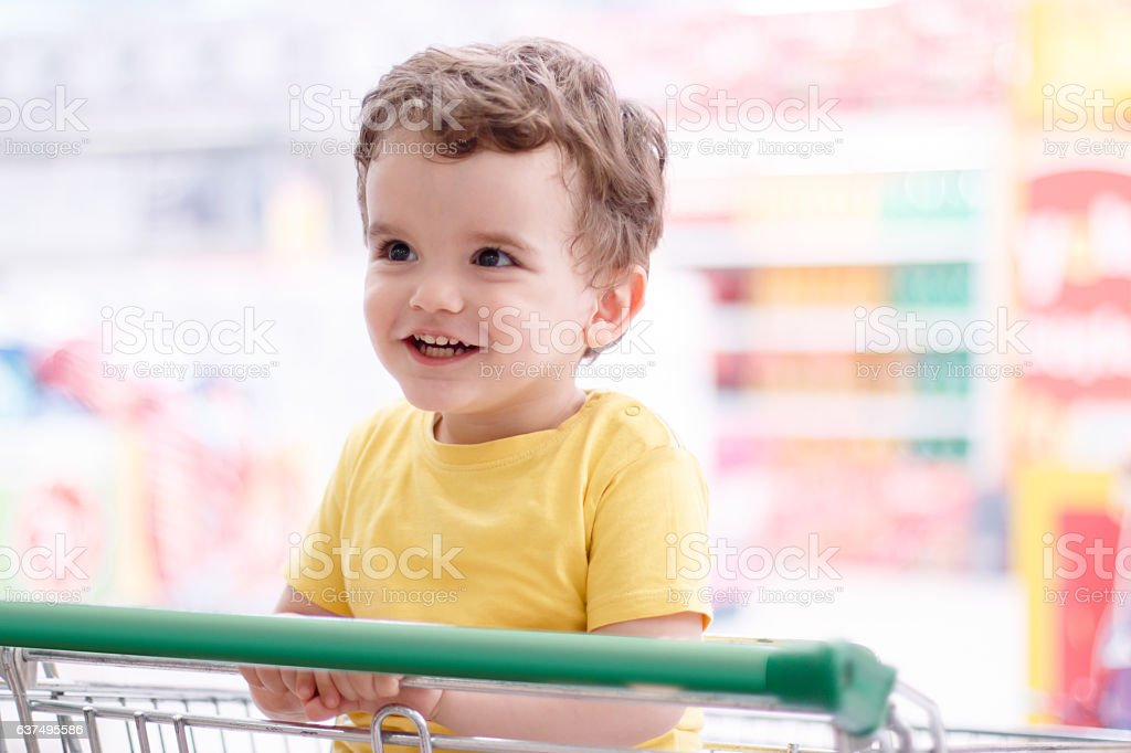 Liitle boy in shopping trolley stock photo