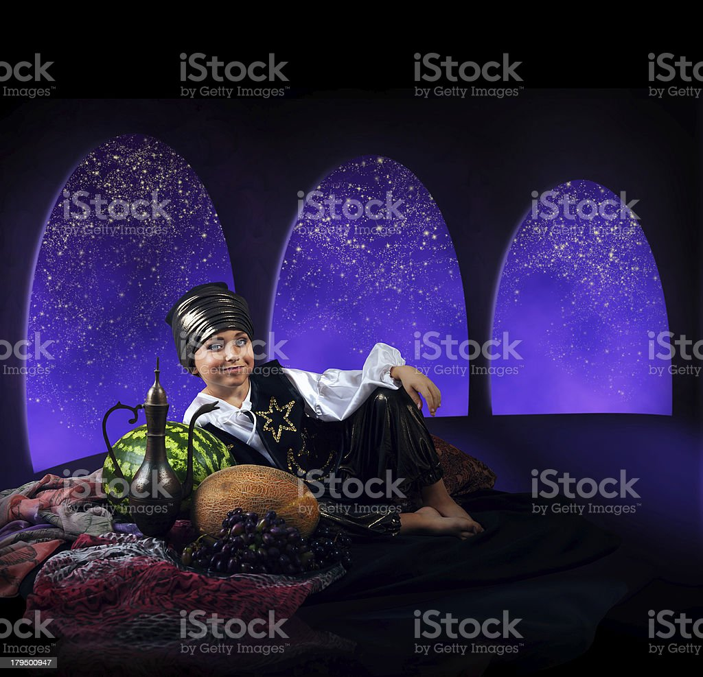 Liitle boy reach orient dress in magic night palace stock photo