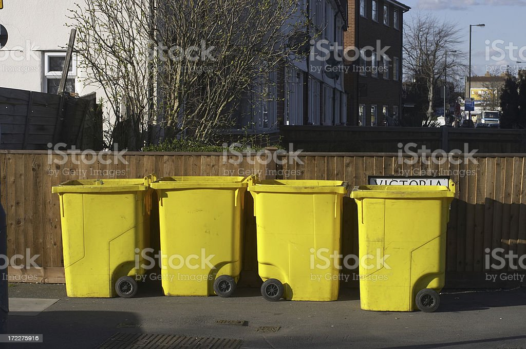 Standing in line four yellow wheelie-bins stock photo