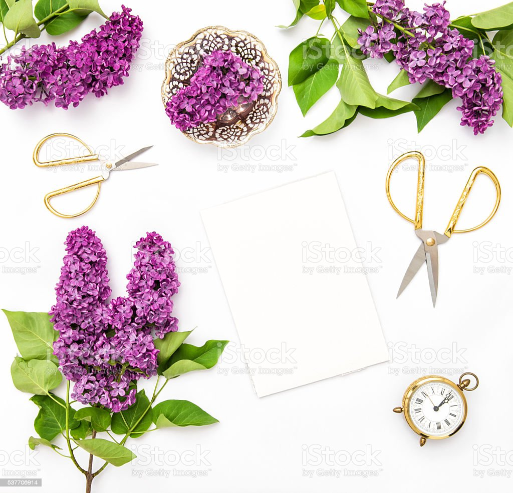 Lilac flowers, sketchbook, office supplies. Flat lay stock photo