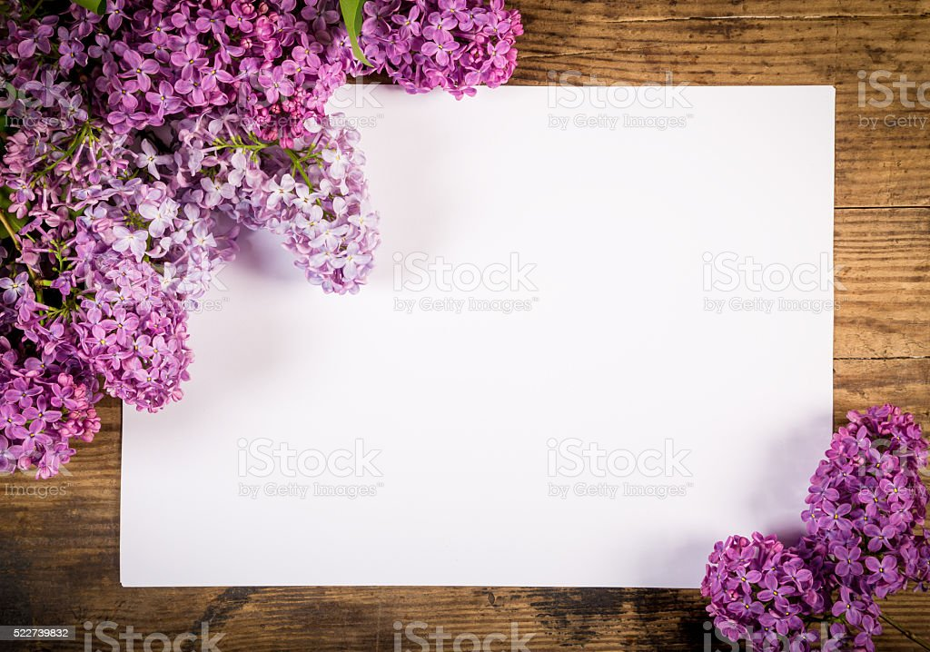 Lilac on old table with blank paper page stock photo