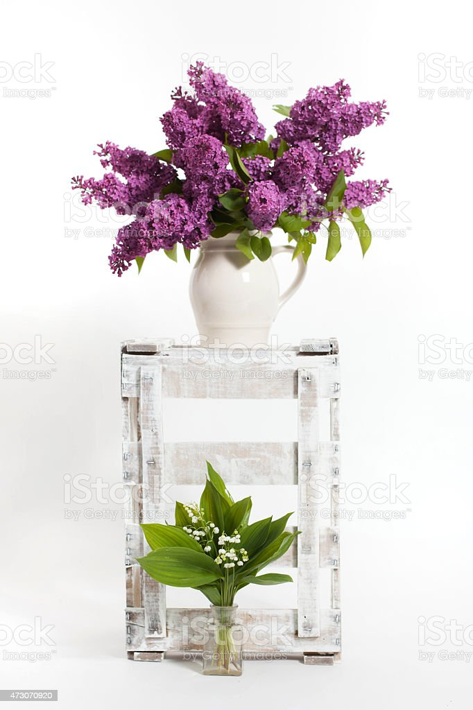 lilacs and lilies of the valley on a wooden crate stock photo