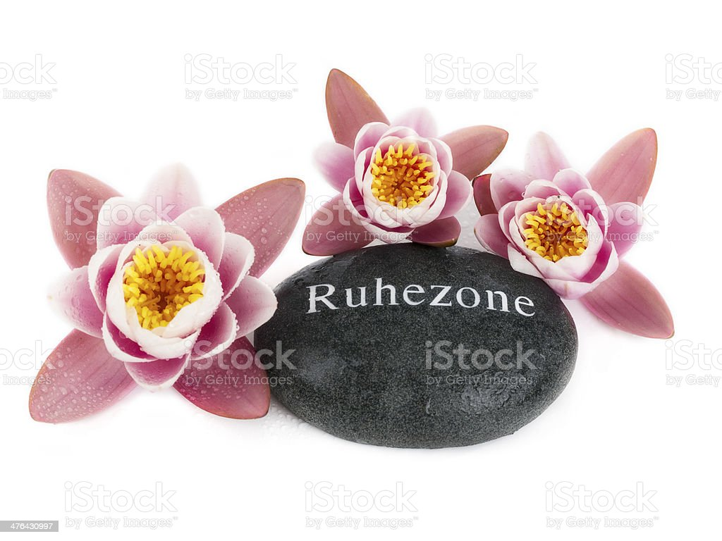 Lily with massage stone in black royalty-free stock photo