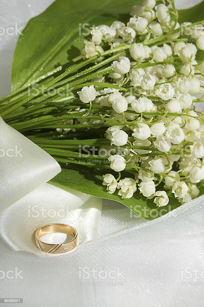 Lily-of-the-valley and wedding ring stock photo