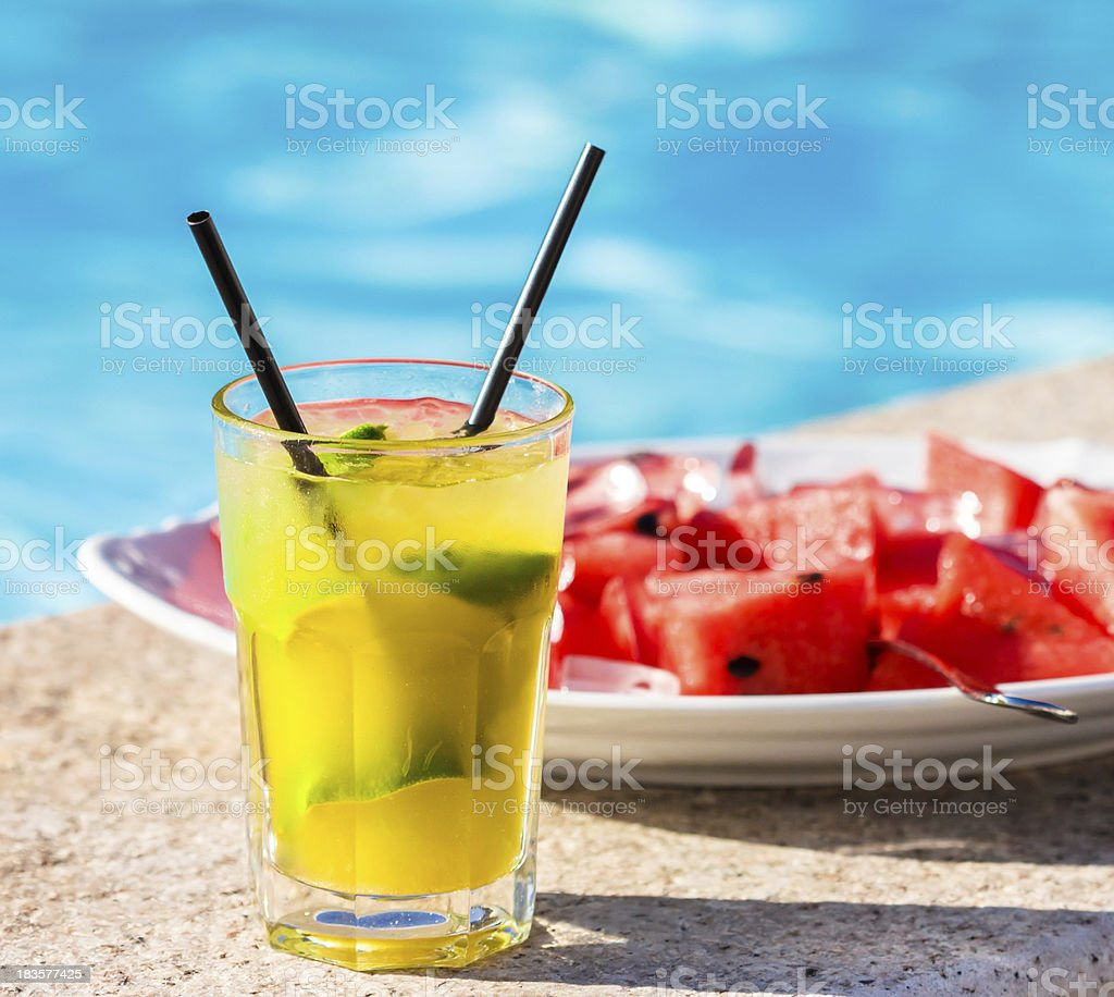 Lime cocktail in front of plate filled with red melon royalty-free stock photo