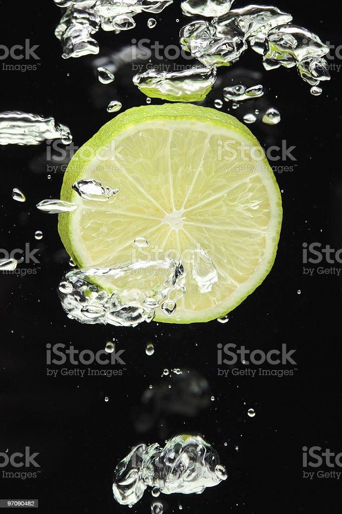 Lime (lemon) falling in water on black background stock photo