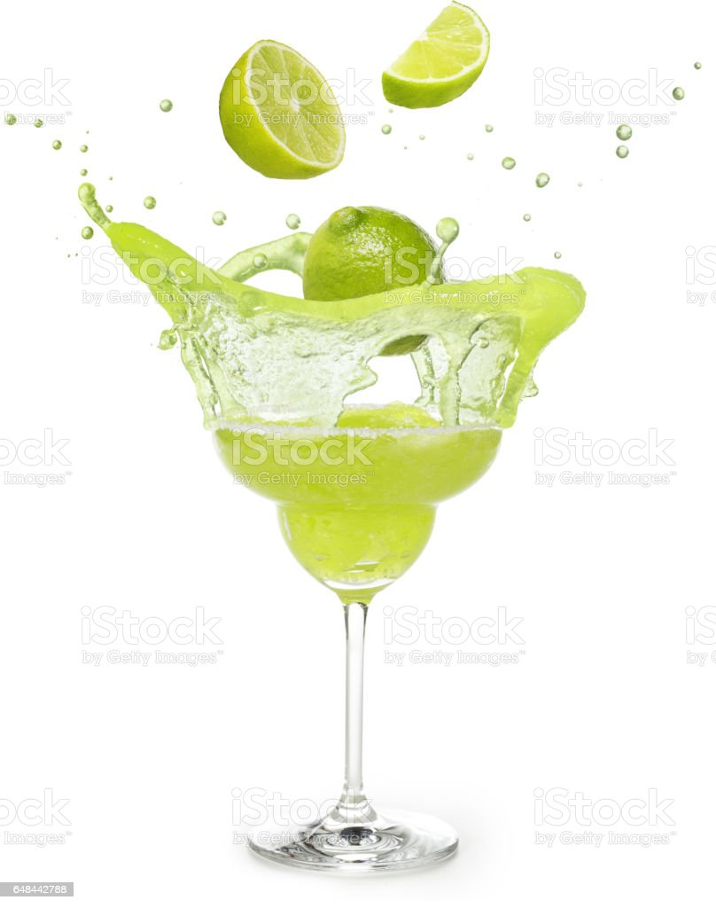 lime falling into a margarita cocktail splashing stock photo