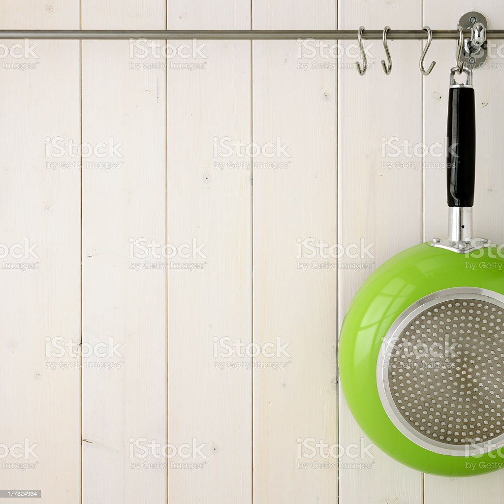 A lime green frying pan hanging up royalty-free stock photo