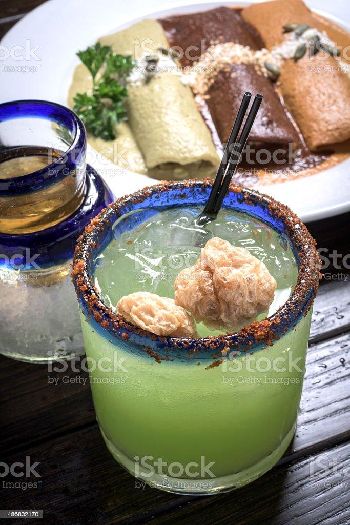Lime margarita, shot of tequila and three moles enchiladas stock photo