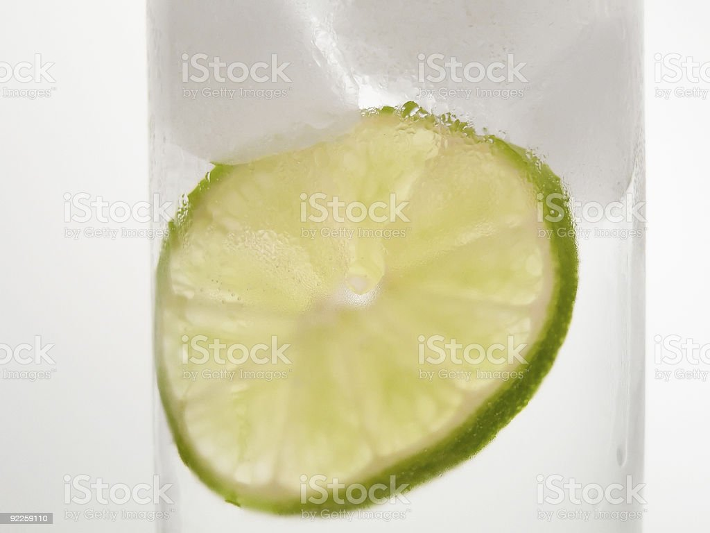 Lime slice in cool glass of water stock photo