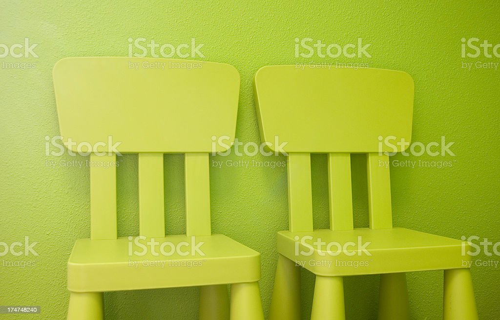 Limegreen kids chairs against lime wall stock photo
