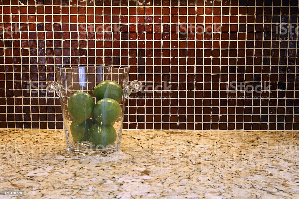 Limes in glass bucket on  modern kitchen counter, splash back. royalty-free stock photo