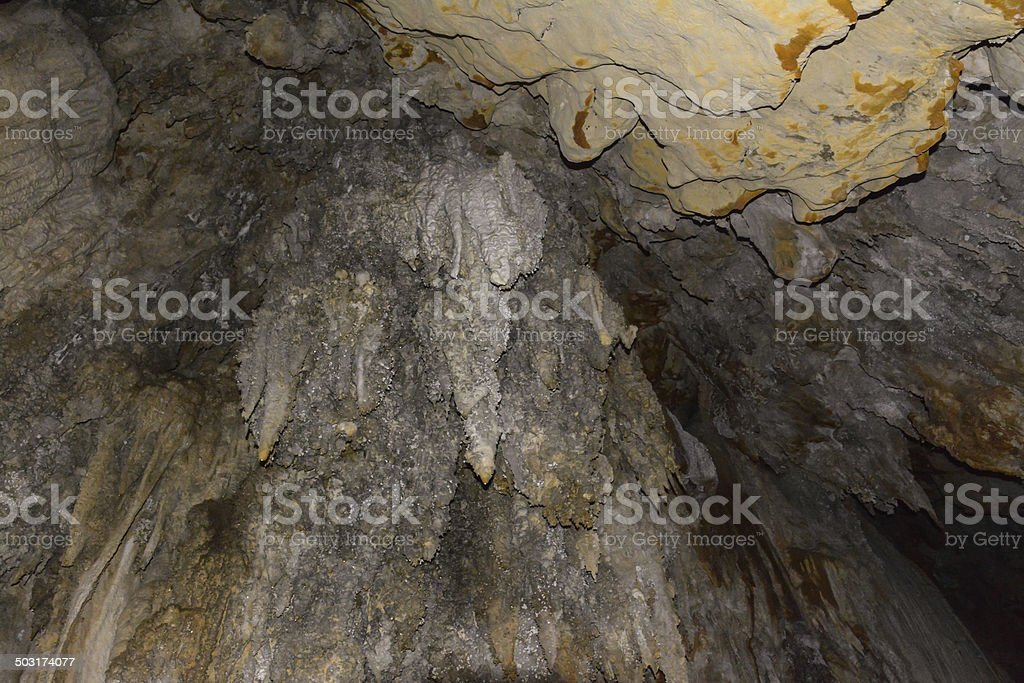 Limestone wall in a cave covered with dripstone stock photo