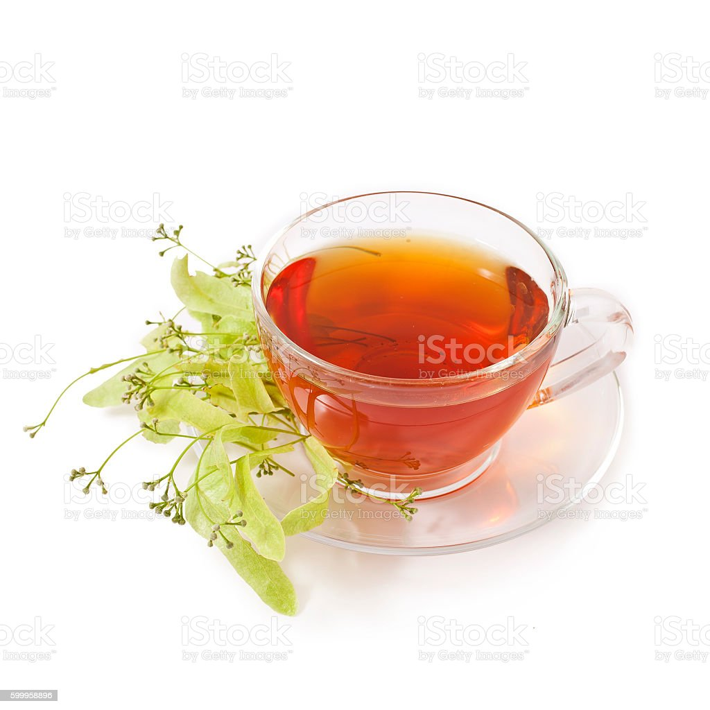 Linden tea in a transparent cup and linden blossoms stock photo