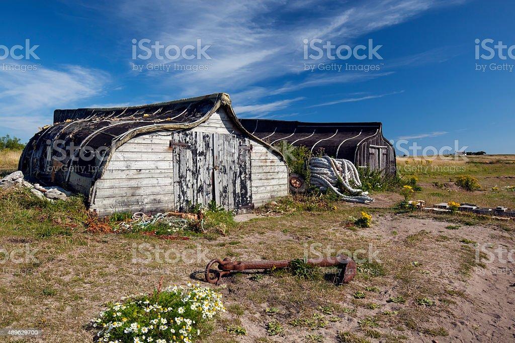 Lindisfarne - Fishermen's storehouses upturned hull of old fishing boats stock photo