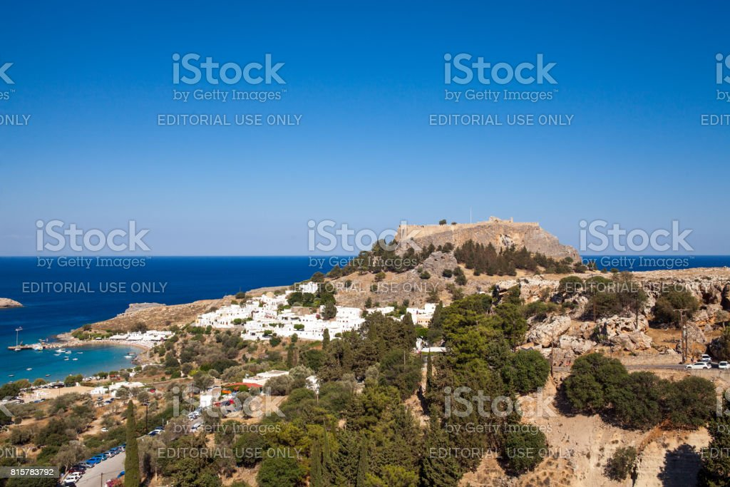 Lindos town at the foot of the mountain. Acropolis of Lindos is located on a hill above the town. Bay and harbor with beach. stock photo