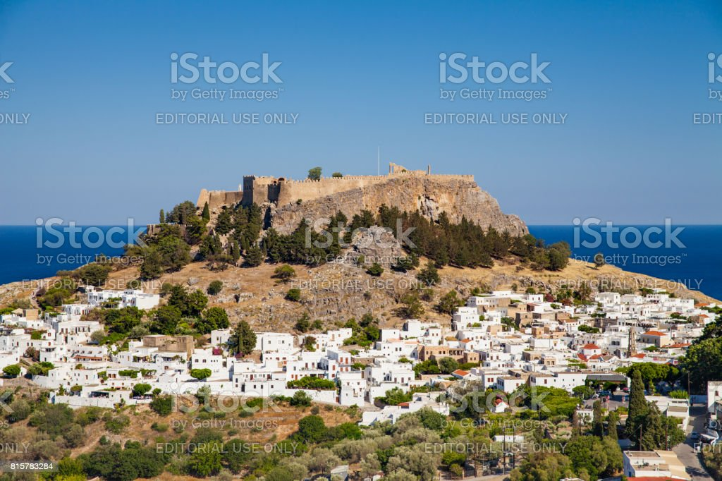 Lindos town at the foot of the mountain. Acropolis of Lindos located on a hill above the town. See on background. stock photo