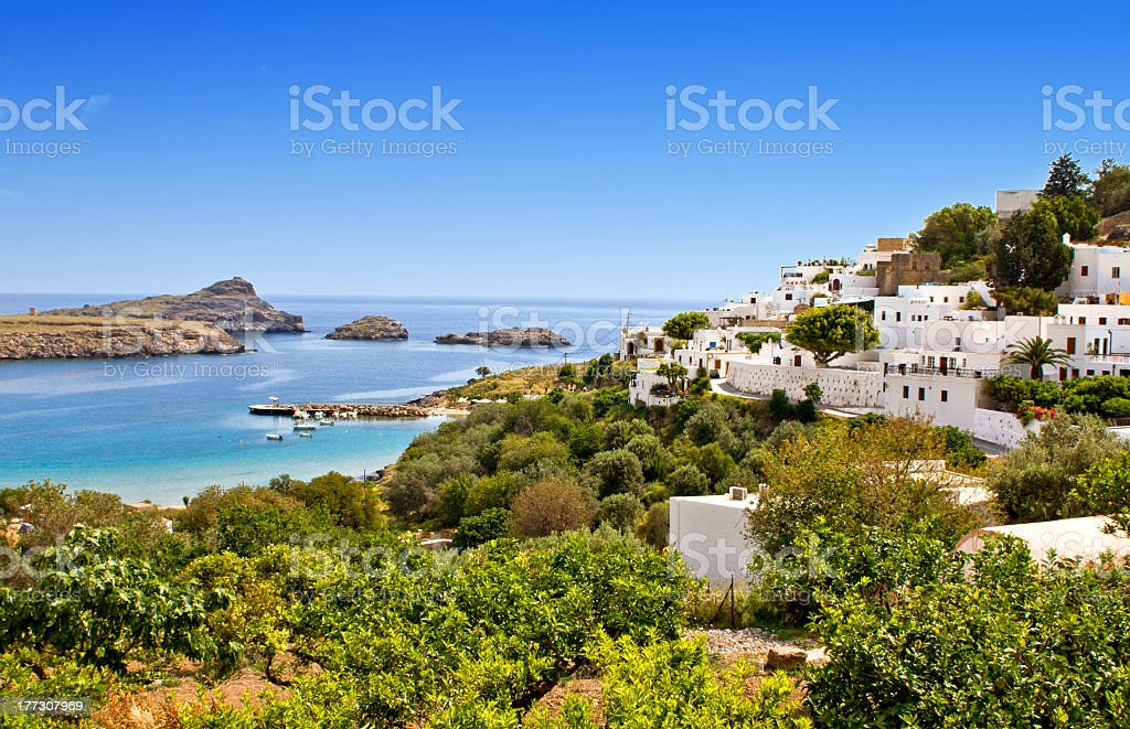 Lindos village in Greece with the blue ocean and green trees stock photo