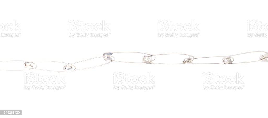 Line border made of multiple safety pins isolated on white stock photo
