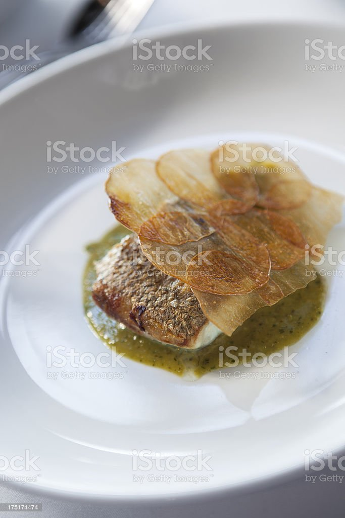 Line caught snapper fillet, crispy potato, nettle & sorrel butter royalty-free stock photo