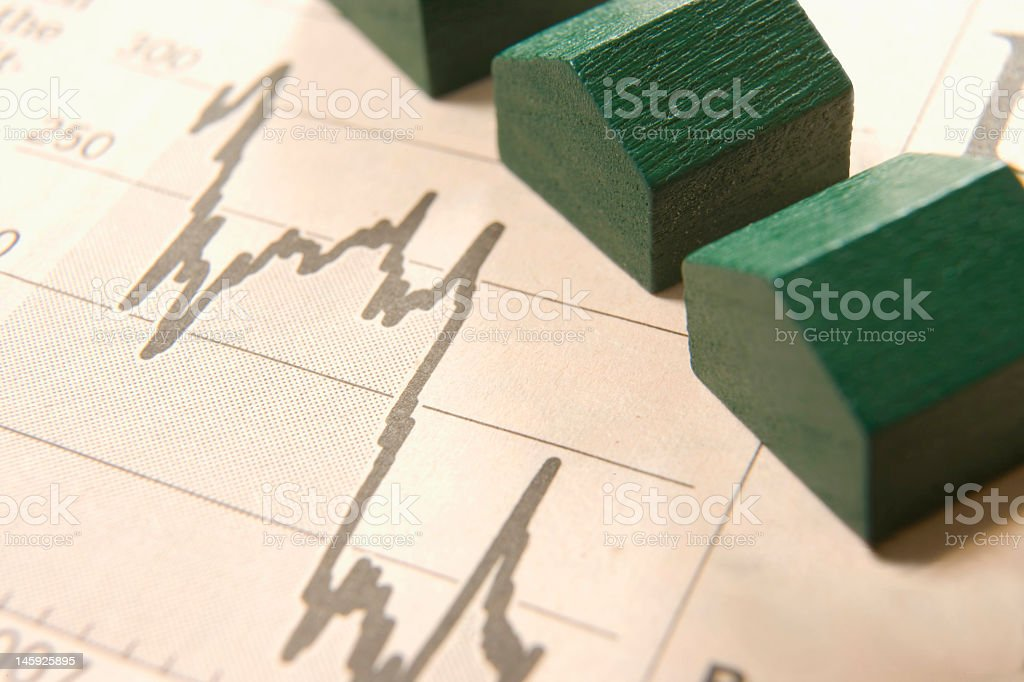 A line graph with small wooden houses placed on top stock photo