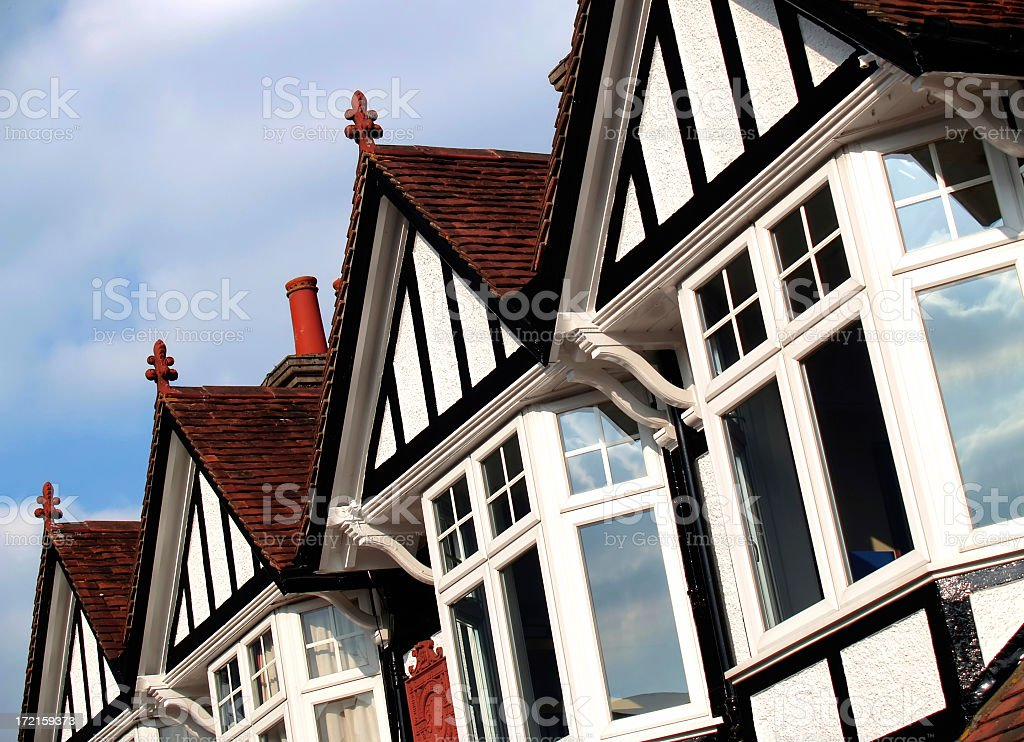 Line of bay windowed cottage homes against blue sky stock photo