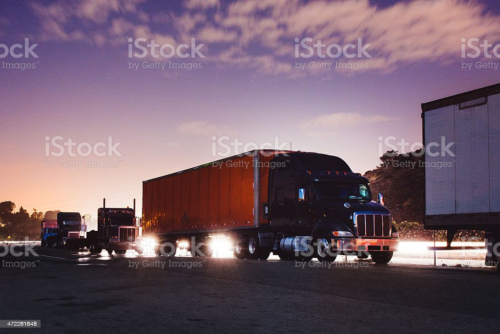 A line of big rig trucks during sun rise stock photo