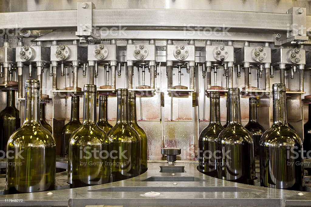 A line of bottles getting corks inserted by a machine stock photo