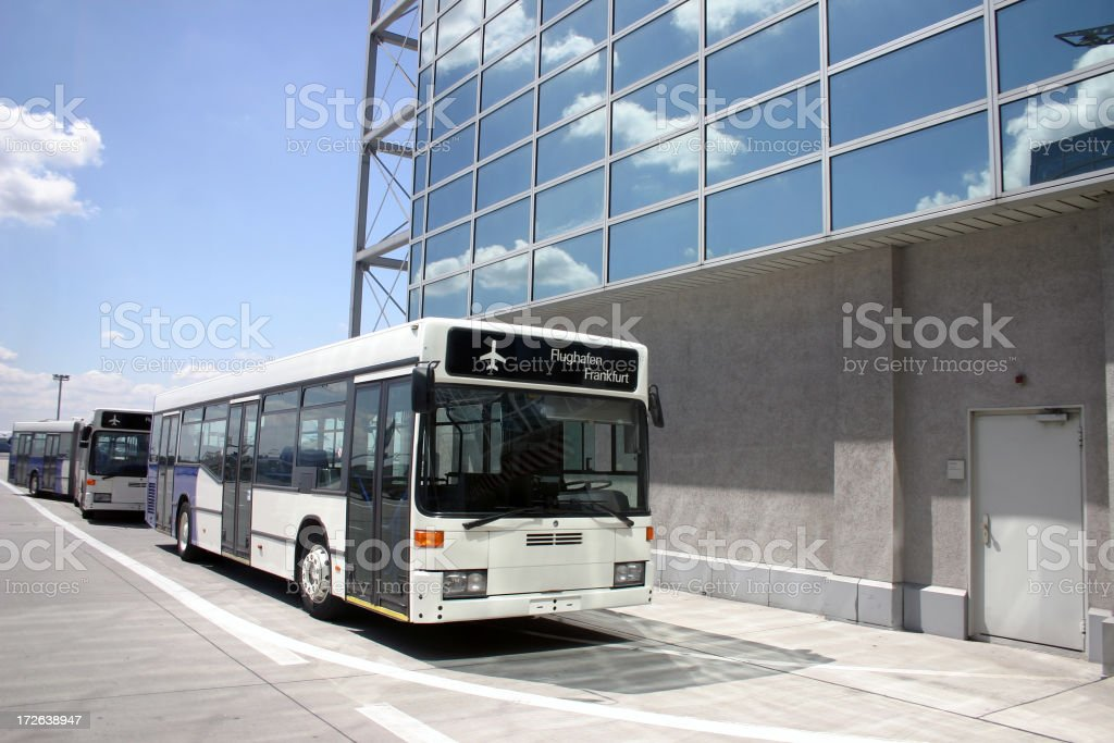 Line of buses by concrete building at airport stock photo