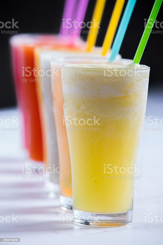 line of cold colorful variety of fruits smoothies in glasses stock photo