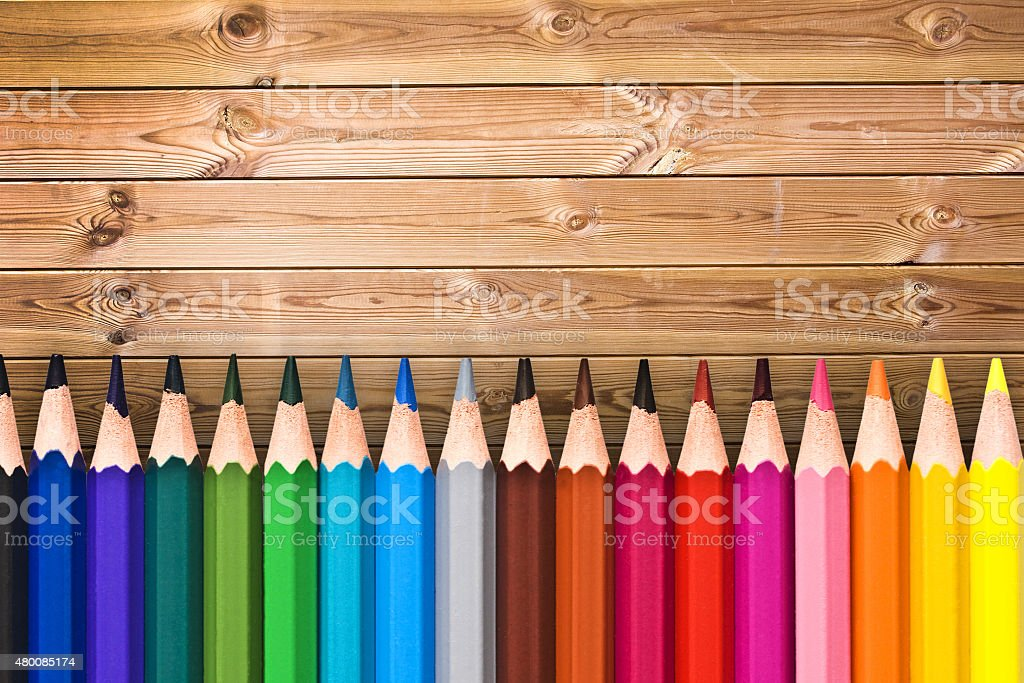 Line of colorful wooden pencils on wood planks background stock photo