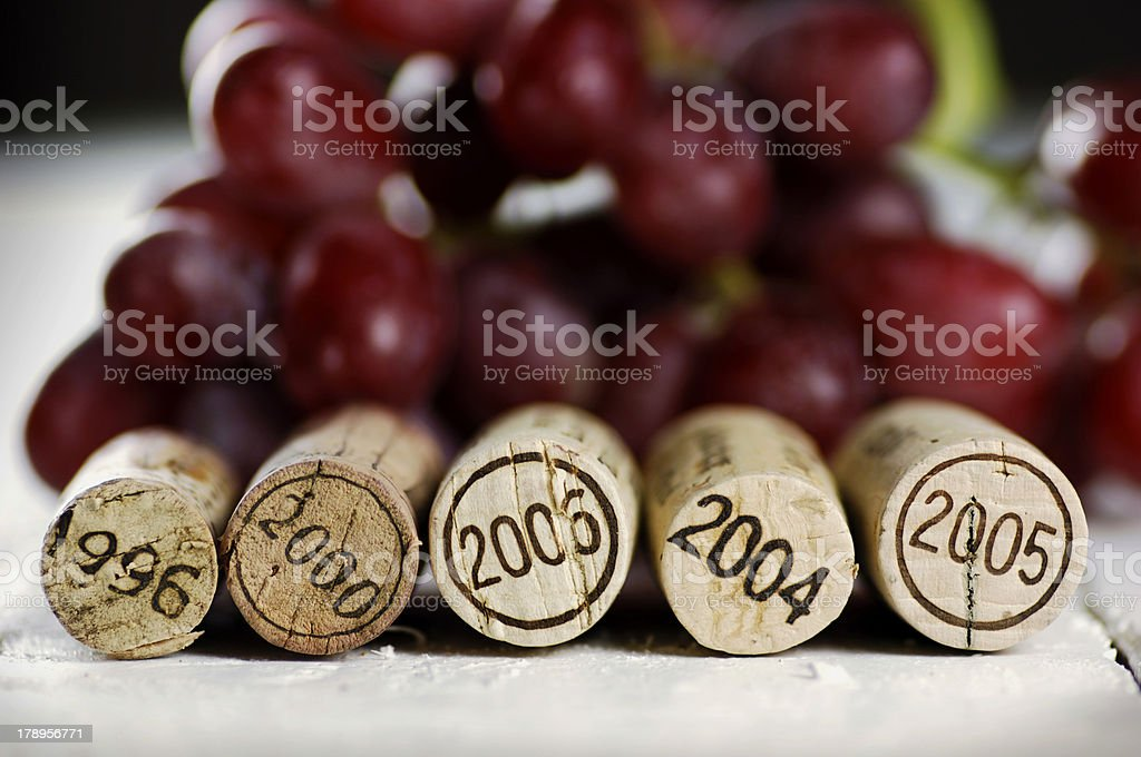 A line of corks and a bunch of grapes royalty-free stock photo
