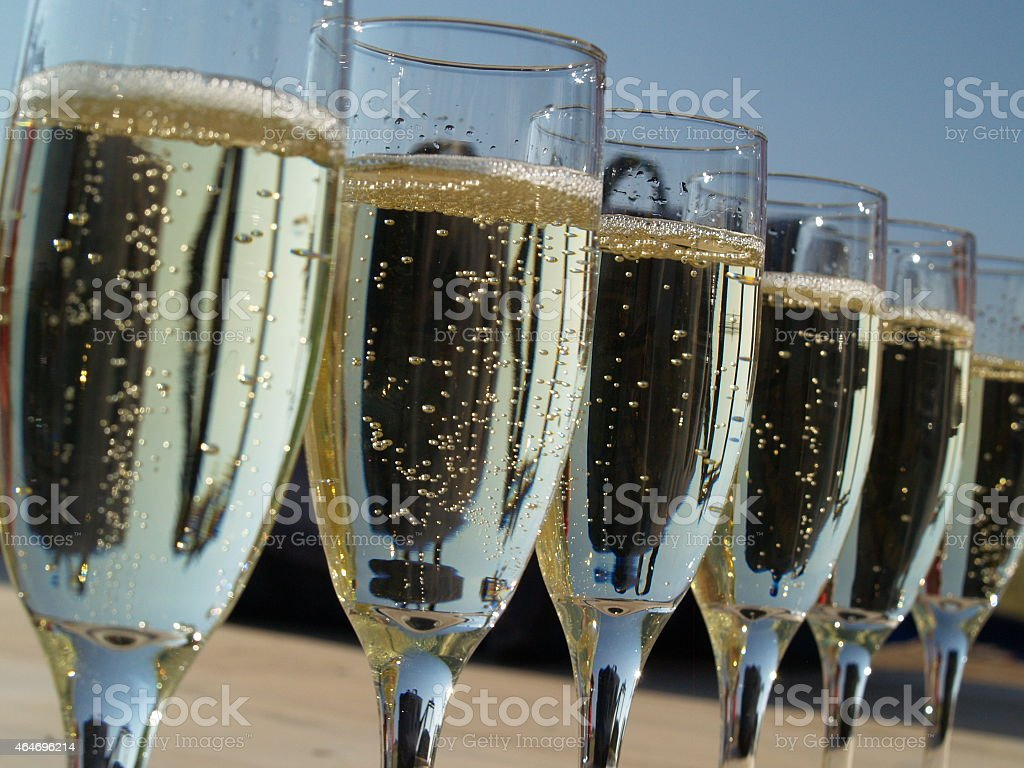 A line of full champagne glasses stock photo