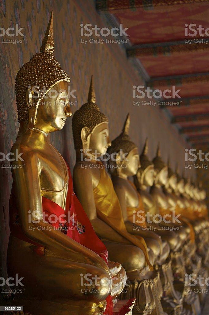 Line of golden Buddha statues in red and orange silk robes stock photo