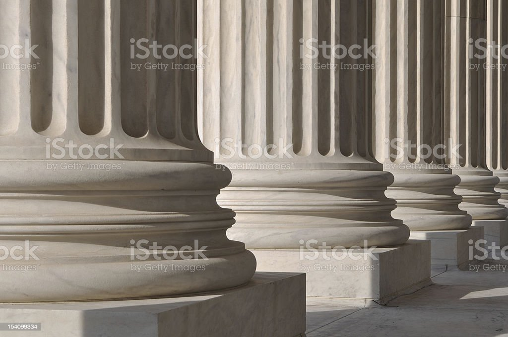 Line of marble pillars with sunlight coming trough stock photo