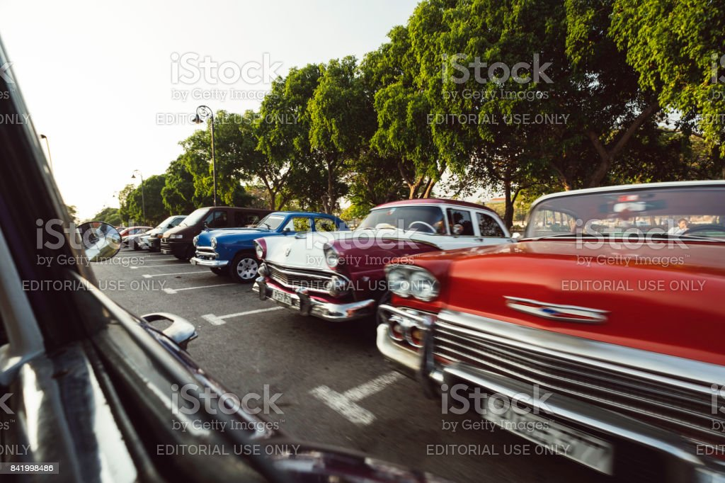 A line of parked classic cars of many colors taken from inside a moving vehicle stock photo