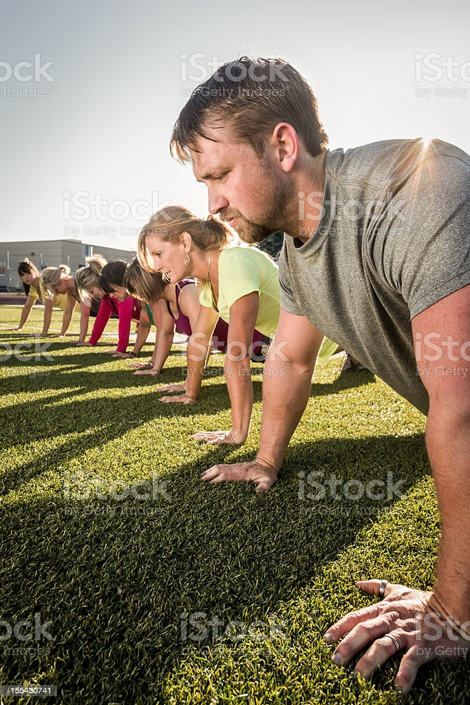 Line of people doing pushups or planks outside on grass royalty-free stock photo