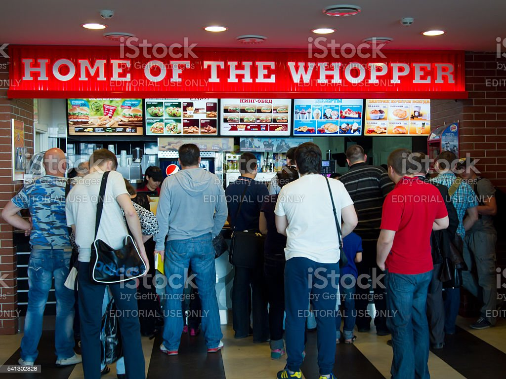 Line of people standing in a cafe Burger King stock photo