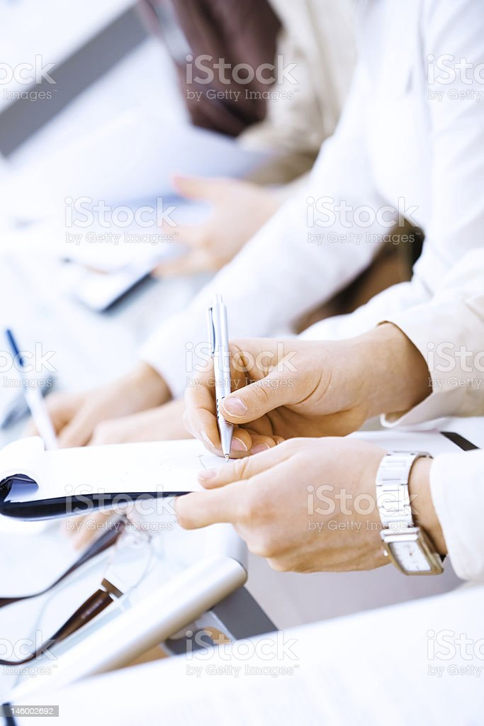 Line of people with notebooks and pens writing notes royalty-free stock photo