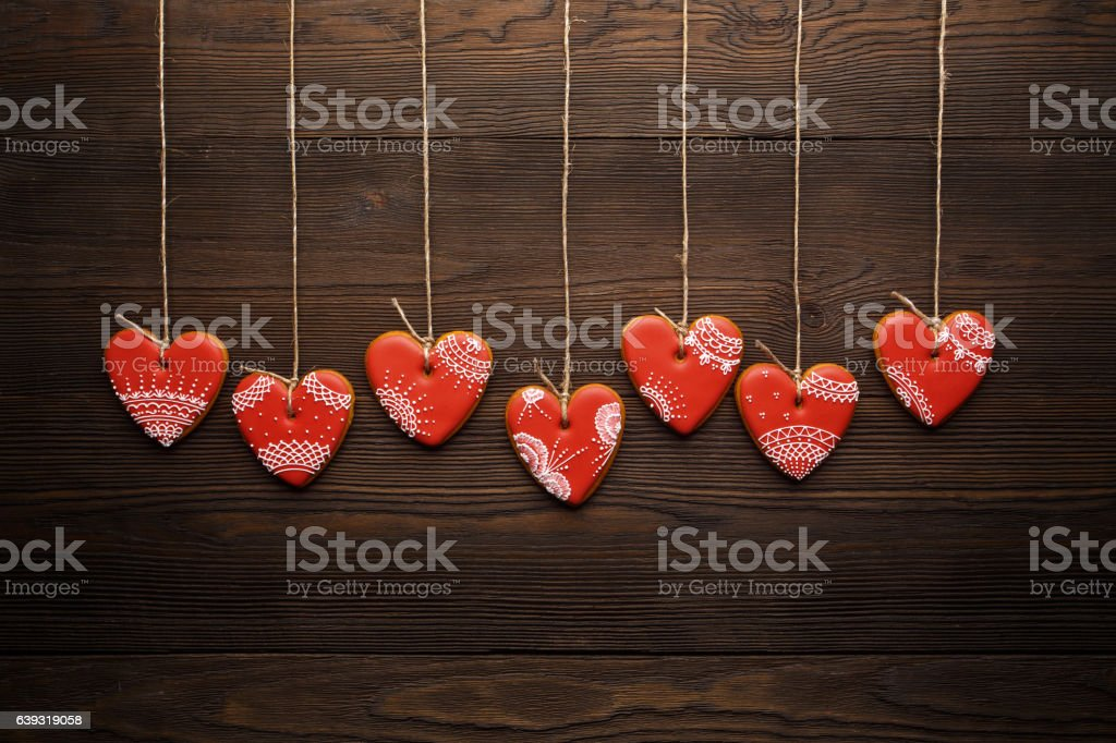 Line of red gingerbreads hearts on ribbon. stock photo