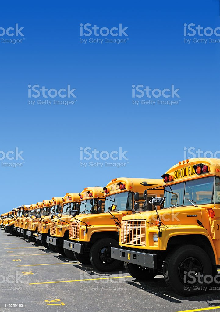 Line of school buses in a parking lot stock photo