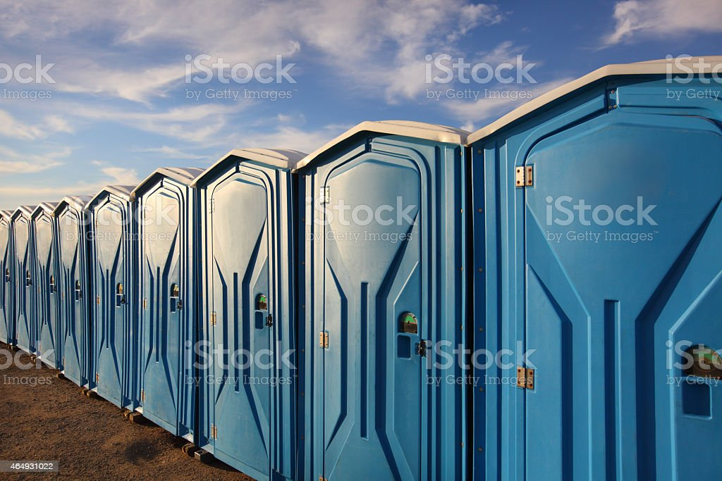 A line of several portable toilets set up in a grassy area stock photo
