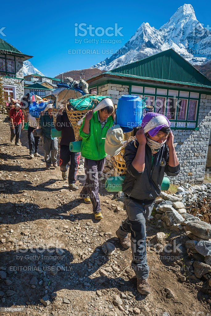 Line of Sherpa porters carrying expedition kit Himalaya mountains Nepal stock photo
