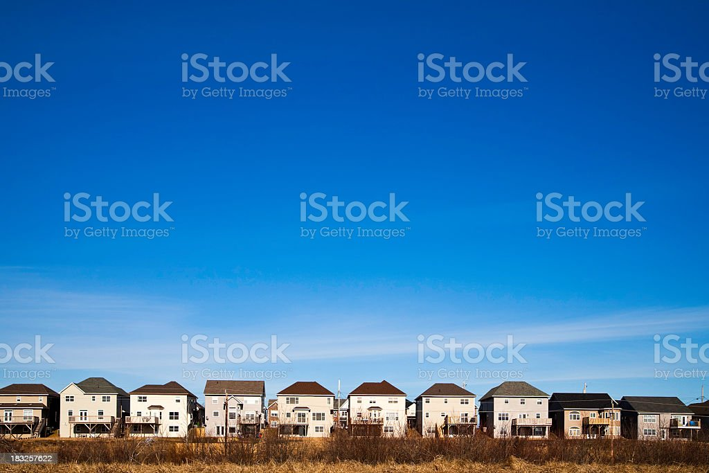 Line of similar white houses with brown roofs under blue sky royalty-free stock photo
