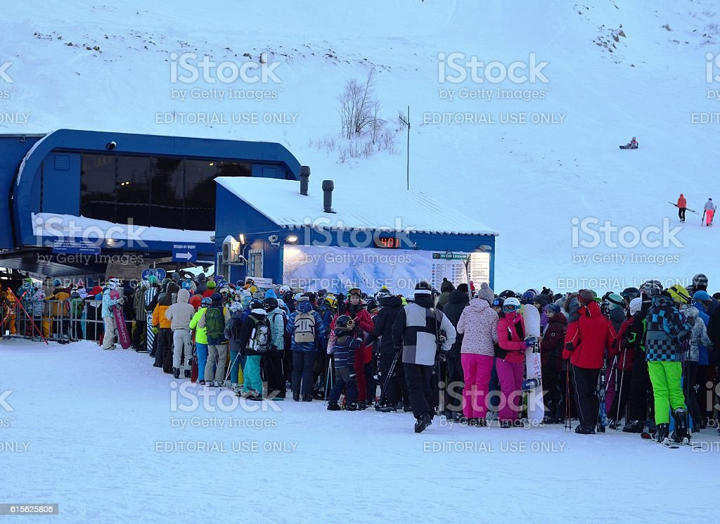 Line of skiers and snowboarders to ski lift stock photo