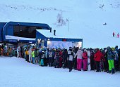 Line of skiers and snowboarders to ski lift