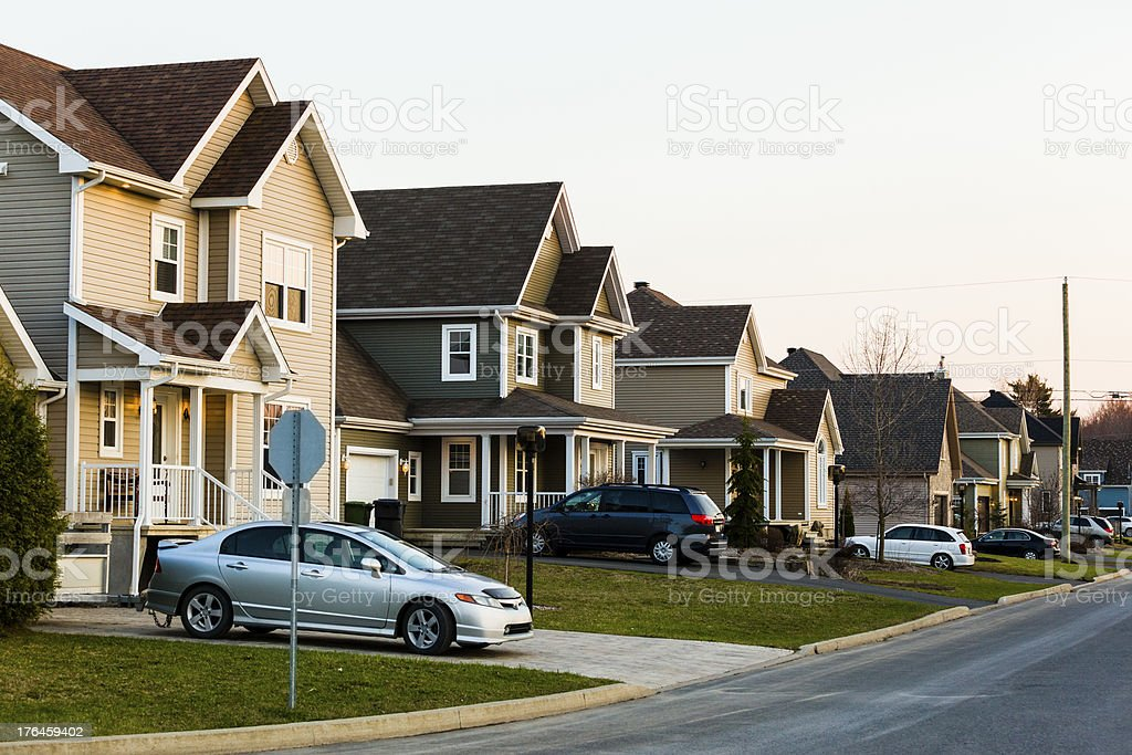 Line of suburb homes each with a car parked in the driveway stock photo