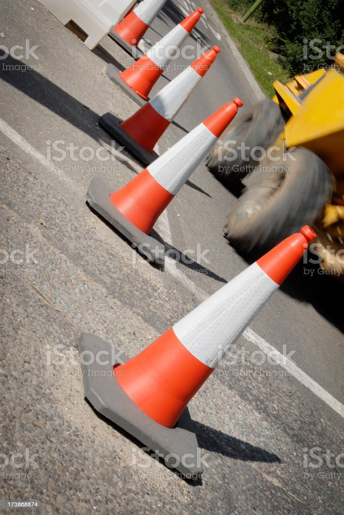 Line of traffic cones protecting road works on busy road royalty-free stock photo