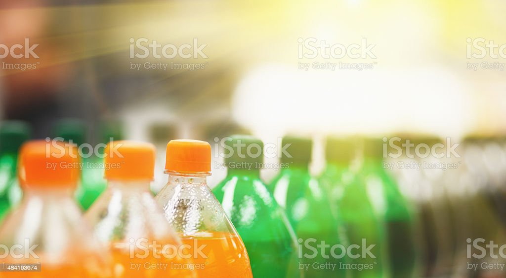 Line of unbranded soda bottles in various flavours at supermarket stock photo